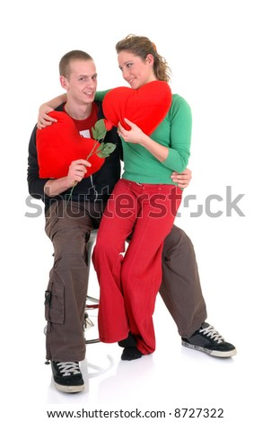 Two casual dressed young adults, teenage man and woman in love, embracing each other. studio shot.