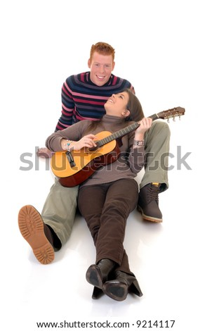 Two casual dressed young adults, teenage man and woman in love, playing the guitar. studio shot, reflective surface