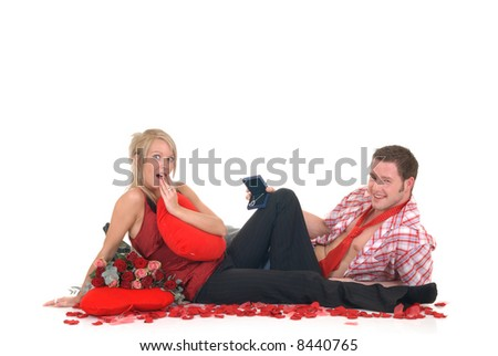 Two casual dressed young adults, teenage man and woman proposing with necklace in box. studio shot, reflective surface - stock photo