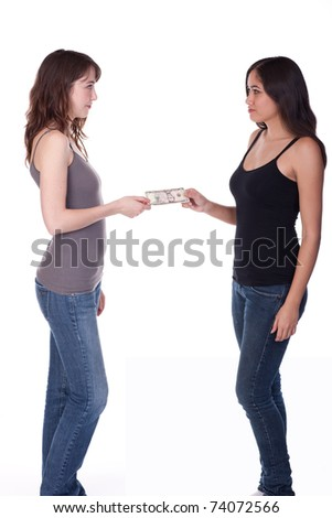 Two casually dressed women standing, exchanging money. - stock photo