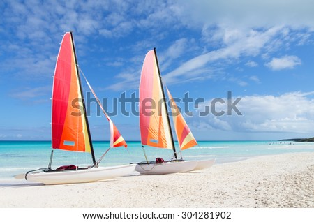 Two catamarans with its colorful sails wide open on Cuban white sandy beach, Cayo Santa Maria - stock photo