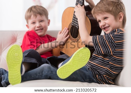 two caucasian boys playing with acoustic guitar. boys sitting on couch and making noise - stock photo