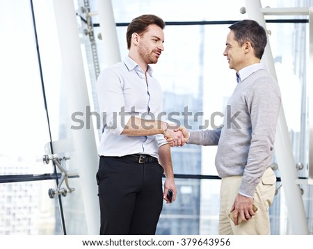 two caucasian business executives in casual wear shaking hands in office. - stock photo
