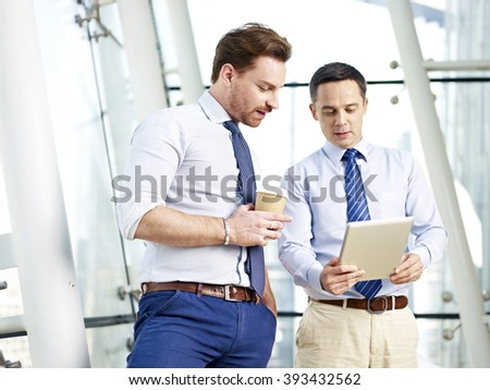 two caucasian business executives looking at and discussing data on tablet computer in office. - stock photo