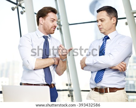 two caucasian business persons standing and chatting in office. - stock photo