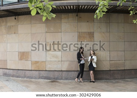 Two Caucasian Business women using digital tablet computer, leaning against a marble wall. - stock photo
