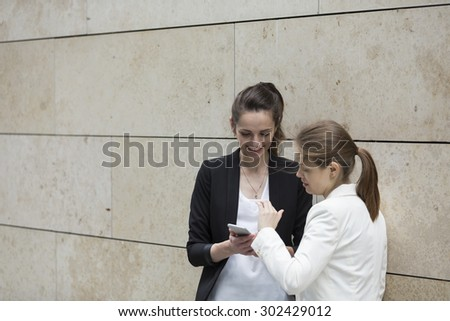 Two Caucasian Business women using Smartphone, leaning against a wall. - stock photo