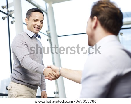 two caucasian businessmen greeting each other by shaking hands in modern office. - stock photo