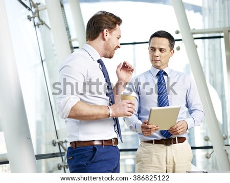two caucasian businessperson having a serious discussion on business in office. - stock photo