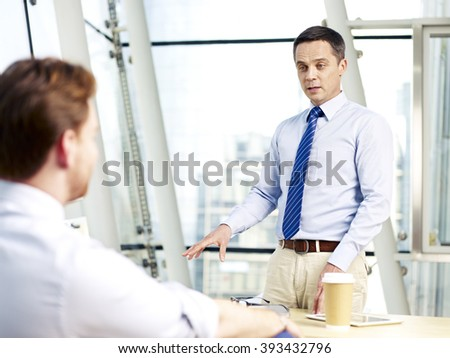 two caucasian corporate executives discussing business in office. - stock photo