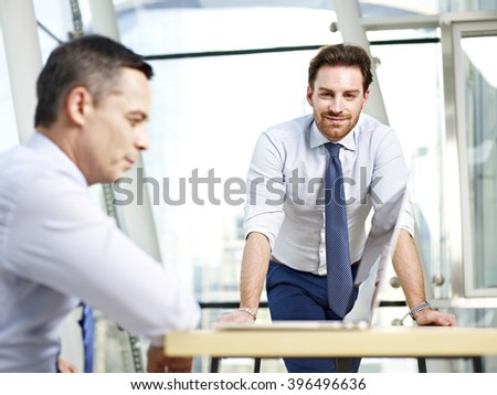 two caucasian corporate people working in office looking at camera smiling. - stock photo