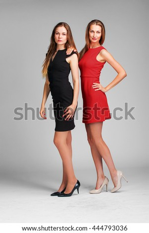 Two Caucasian  fashion models posing in studio on grey background
