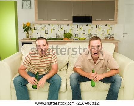 two caucasian men sitting on couch watching television and holding beers, in kitchen, one of them acting surprised, the other drunk - stock photo