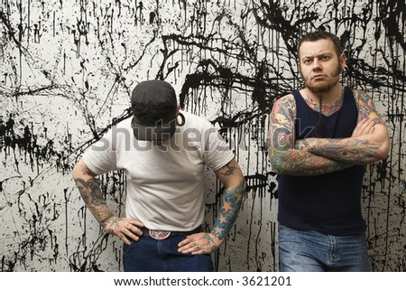 Two Caucasian tattooed men standing against paint splattered background.