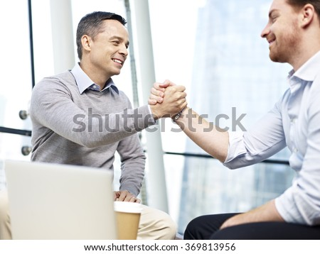 two caucasian teammates coworkers celebrating partnership and success by holding hands in office. - stock photo