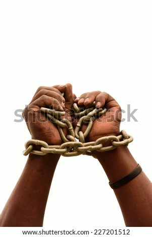 Two chained black male hands of a young South African Xhosa imprisoned man. Image isolated on white studio background. - stock photo