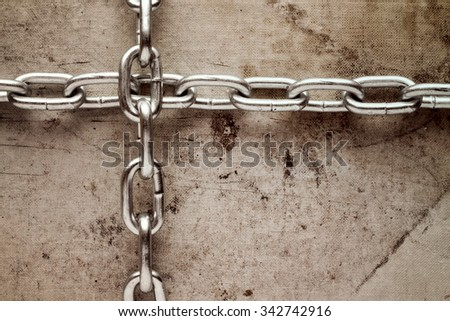 Two chains crossed on old canvas background. Grunge style image. - stock photo