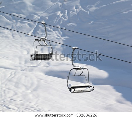 Two chair-lift with snowdrift and off-piste slope in sun morning. Caucasus Mountains. Georgia, ski resort Gudauri. - stock photo