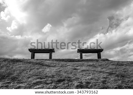 Two chair on the park sky and white cloud, selective focus, B&W - stock photo