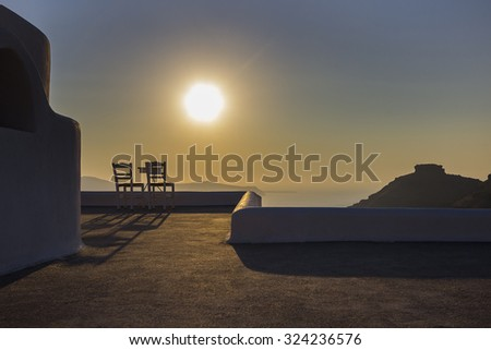 Two chairs and a small table on a beautiful terrace with a wonderful view behind the sunset in Santorini - Greece.