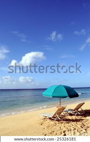 Two chairs and an umbrella on the beach in Waikiki Beach, Honolulu, Hawaii - stock photo