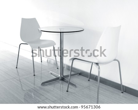 Two chairs and glass coffee table - stock photo