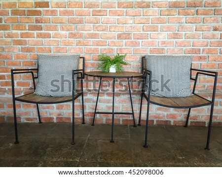 Two chairs and table with brick wall