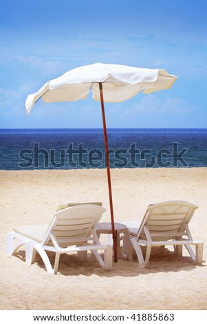 Two chairs and umbrella - stock photo