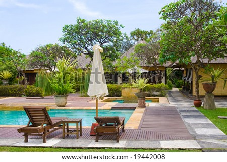 Two chairs and umbrella by the swimming pool - stock photo