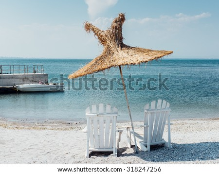 Two chairs and umbrella on a beach vacation destination, with boat on background