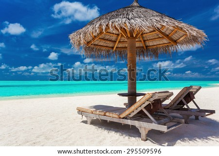 Two chairs and umbrella on a tropical beach with amazing lagoon view - stock photo