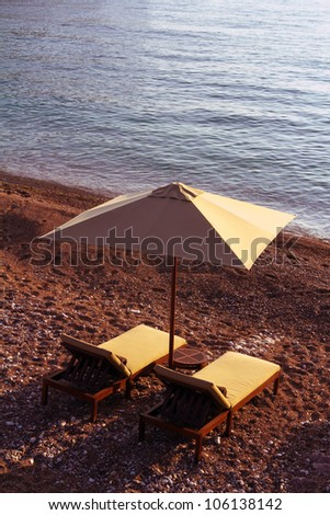 Two chairs and umbrella on Sveti Stefan beach - stock photo