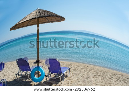 Two chairs and umbrella on the beach - fisheye effect - stock photo