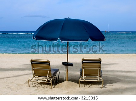 Two chairs and umbrella on the beach in hawaii - stock photo