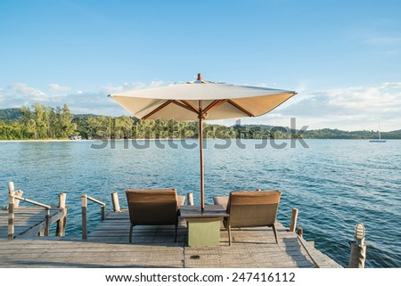 Two chairs beach and umbrella on wooden desk against blue sky.Summer Travel in Phuket ,Thailand. - stock photo