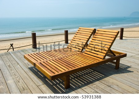 Two chairs by the beach shore. - stock photo