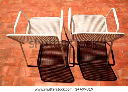 two chairs for a sunbath on the terrace, nice shadows - stock photo