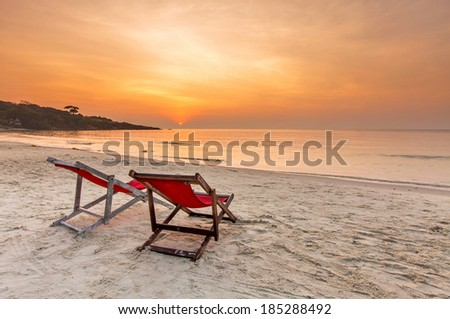 Two chairs on the beach over the sunset