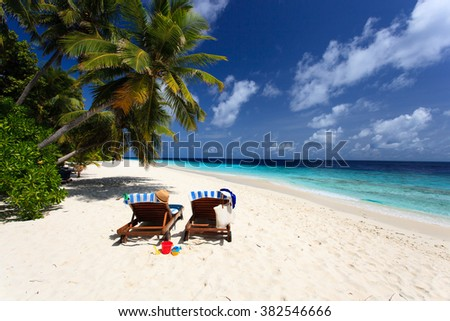 Two chairs on tropical beach, family vacation