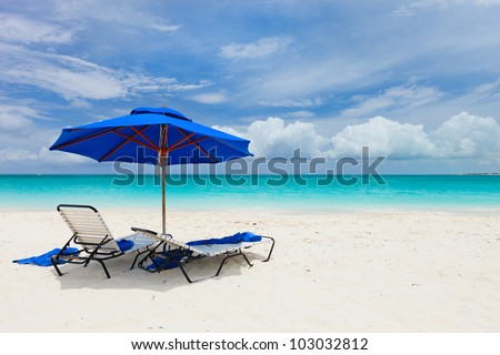 Two chairs under umbrella on beautiful tropical beach in Turks and Caicos - stock photo