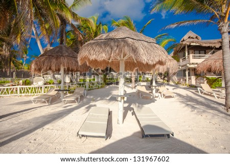 Two chaise lounges under an umbrella on sandy beach - stock photo