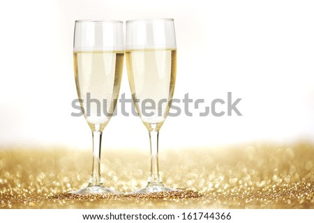Two champagne flutes on gold shiny background - stock photo