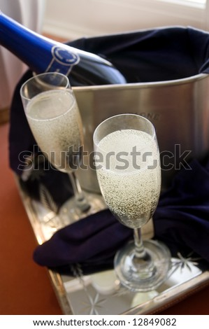 two champagne glasses and bottle in ice bucket, only front glass is sharp - stock photo