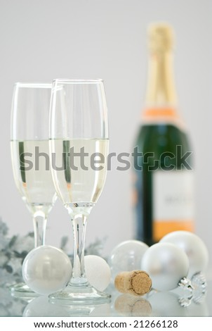 Two champagne glasses and bottle of champagne in background with Christmas decorations - stock photo