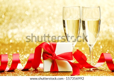 Two champagne glasses and gift on golden background