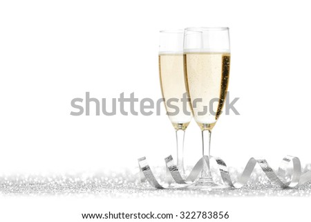 Two champagne glasses and silver ribbon on white background - stock photo