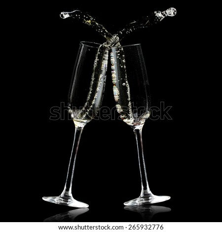 Two champagne glasses isolated on black with splashes - stock photo