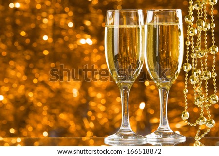 Two Champagne glasses on light bokeh background