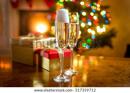 Two champagne glasses on table against fireplace decorated for Christmas - stock photo
