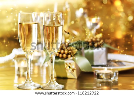 Two champagne glasses on the dinner table with gift boxes - stock photo